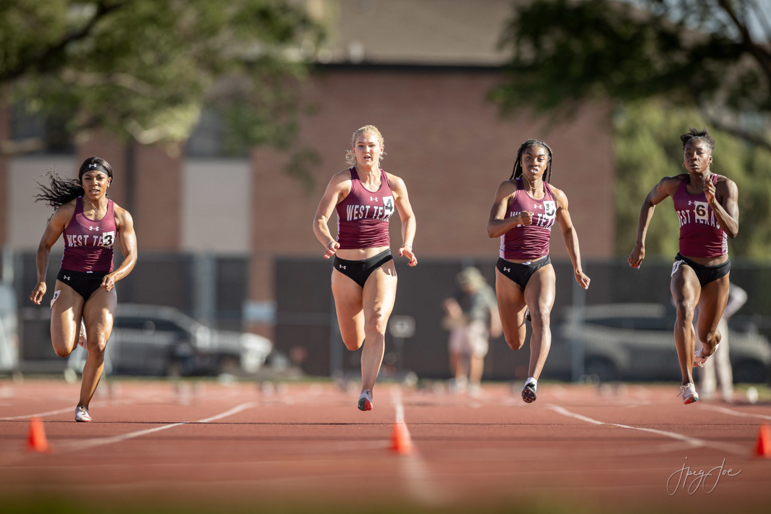A group of WTAMU female athletes run down the track at the 2021 Lone Star Conference Track meet.